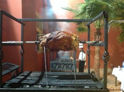 Les cuisiniers ne travaillent pas toujours dans l'ombre. Ici, au beau milieu du restaurant, une grosse pièce de viande tourne à la broche.