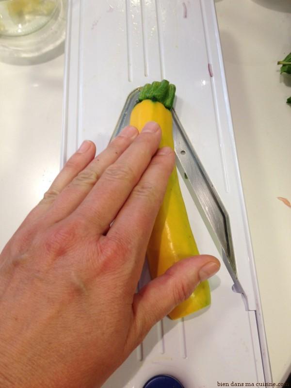 """La main bien à plat sur la courgette, faites glisser celle-ci sur le """"V"""" avec les lames. Attention les doigts, ça coupe vite !"""