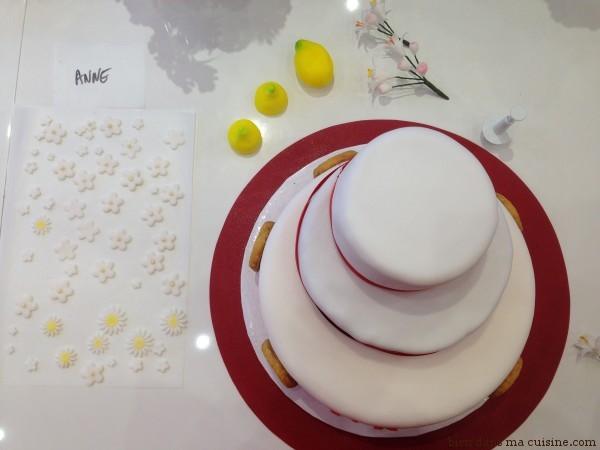 16. On ressort le premier gâteau du frigo, on le colle sur le socle avec un gros point de glucose liquide. Puis on fait de même avec le second gâteau. Oh ! C'est beau ! On termine en collant les fleurs et autres petites déco avec du glucose, on rajoute des déco en sucre si on veut (ici des citrons, pour rappeler les palets au citron du départ)... Et on admire !